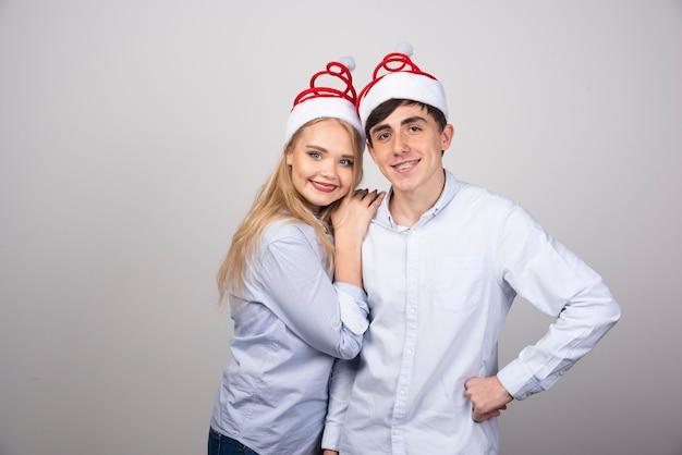 Ritratto di giovane coppia in cappello della santa che posa felicemente sulla parete grigia.