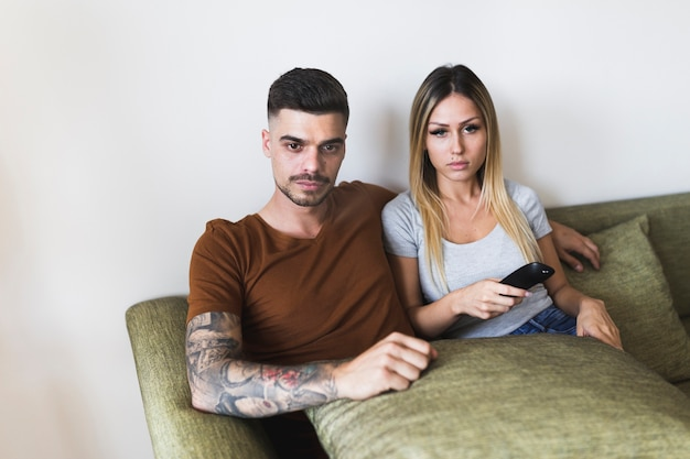 Portrait of young couple sitting on couch watching television