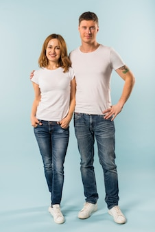 Portrait of a young couple standing against blue background