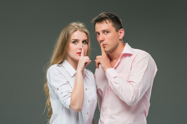 Portrait of a young couple standing against gray background