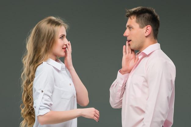 Ritratto di una giovane coppia in piedi contro il muro grigio