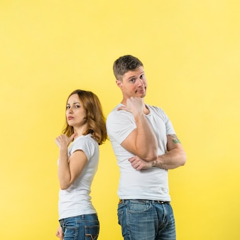 Portrait of young couple standing back to back showing thumb up sign to each other