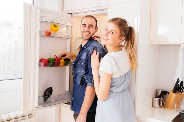 Portrait of young couple standing in front of an open refrigerator with vegetables