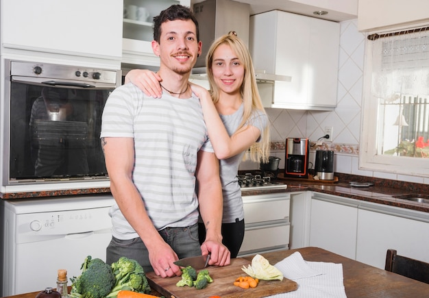 Portrait of young couple standing in the kitchen