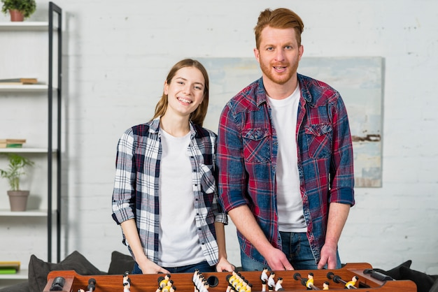 Portrait of young couple standing behind the table soccer game in the living room