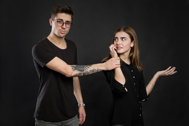 Portrait of a young couple standing with mobile phone, girl holding mobile phone while frustrated man standing near isolated over black background