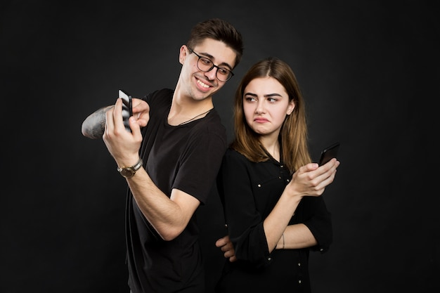 Portrait of a young couple standing with mobile phone, man is playing games on mobile phone while angry girl standing near isolated over black wall