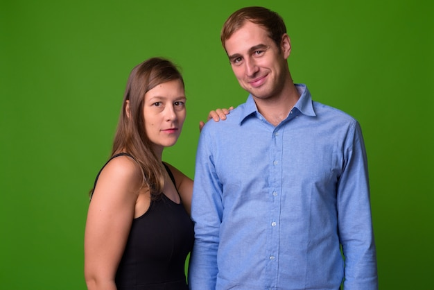 Portrait of young couple together against green wall
