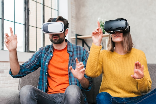 Portrait of young couple touching in air wearing the virtual reality glasses