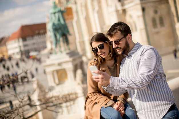 Portrait of young couple of tourist in town using mobile phone