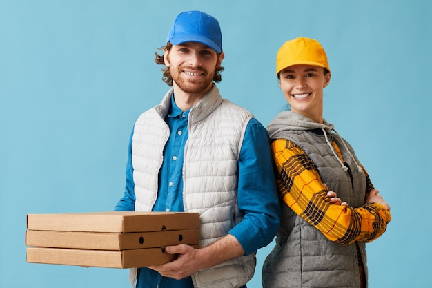 Portrait of young couple in uniform delivering pizza and smiling at camera against the blue background