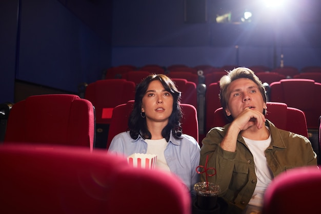 Portrait of young couple watching movie in cinema while enjoying private viewing in empty hall, copy space