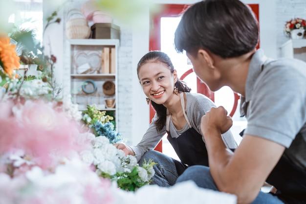 花屋で一緒に働いている間話しているエプロン笑顔の肖像画の若いカップル