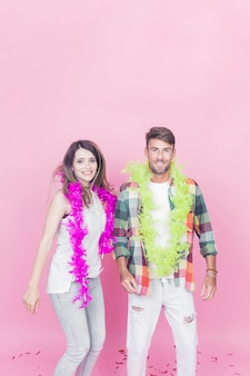 Portrait of young couple wearing boa around their neck against the pink background