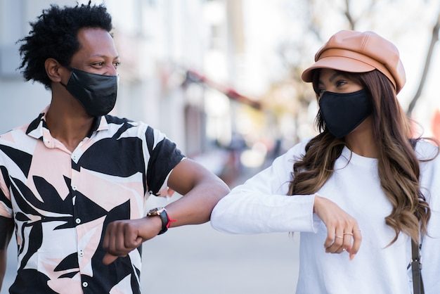 Portrait of young couple wearing face mask and tapping each other with their elbows to say hello while standing outdoors. new normal lifestyle concept.