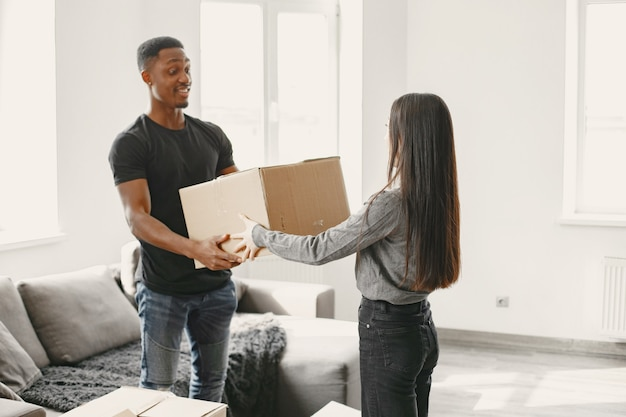 Portrait of young couple with cardboard boxes at new home, moving house concept.