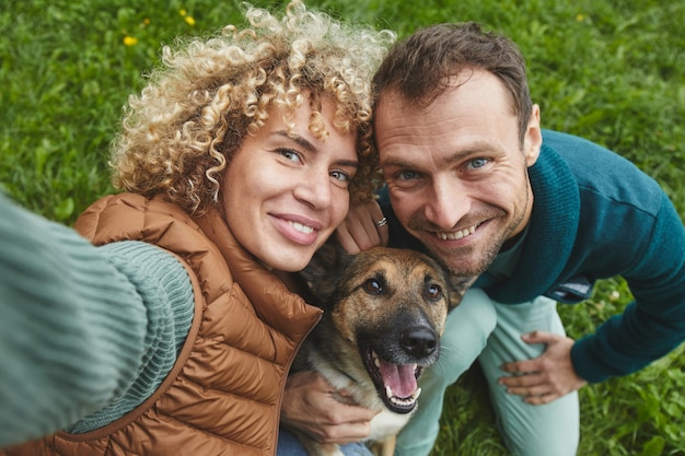 Portrait of young couple with dog smiling at camera while walking on the nature