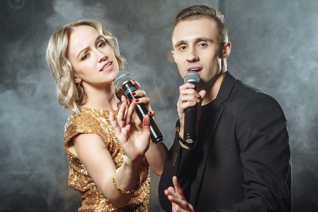 Portrait of a young couple with microphones