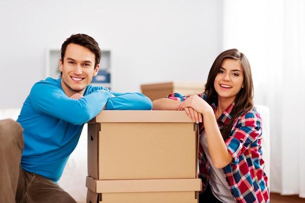 Ritratto di giovane coppia con contenitori per il trasloco