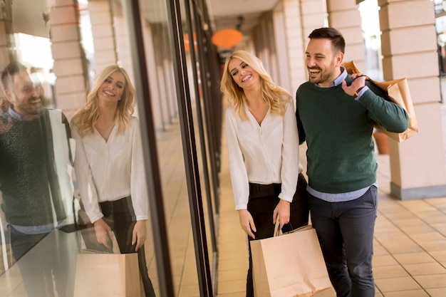 Portrait of young couple with shopping bags in city