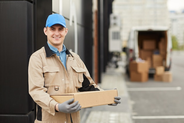Portrait of young courier in uniform holding box and smiling at camera while standing outdoors