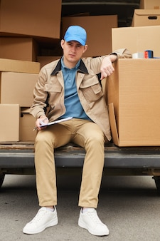 Portrait of young courier in uniform sitting with document and looking at camera while delivering the parcels