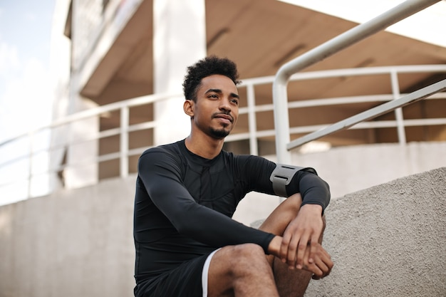 Portrait of young curly bearded dark-skinned man in black long-sleeved t-shirt and shorts sitting on stairs outside