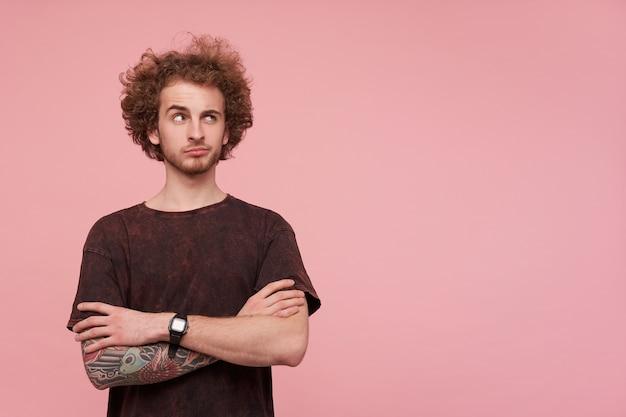 Ritratto di giovane uomo tatuato barbuto riccio guardando pensieroso verso l'alto con un sopracciglio alzato, tenendo le mani sul petto mentre si sta in piedi sopra il muro rosa