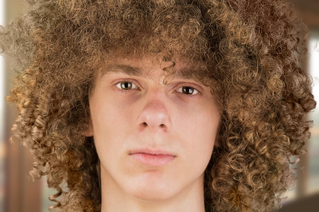 Portrait of a young curly european man with long curly hair and a defiant gaze looks into the frame close-up
