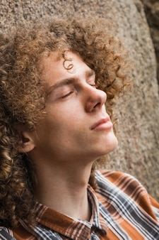 Portrait of a young curly haired guy among the stones