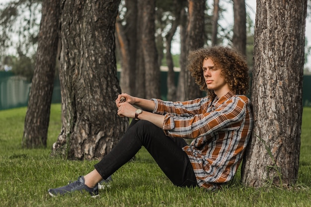 Portrait of a young curly haired guy in a summer park