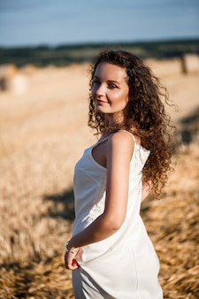 Portrait of a young curly woman in a wheat field, where the wheat is mown and the sheaves are standing, enjoying nature. nature. sun rays agriculture