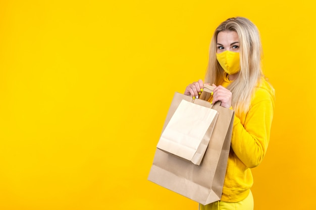 Portrait of young cute blonde woman with paper eco-bag in yellow protective mask