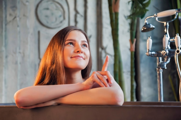 Portrait of young cute cheerful woman in bathtub shows finge and looking away over old interior bathroom. advertising concept of healthy lifestyle and self care. copy space for site or spa