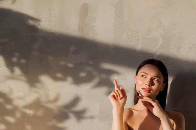 Portrait of young cute cheerful woman shows finger and looking away over old wall background with shade from leaf. advertising concept of healthy lifestyle and self care. copy space for site or spa