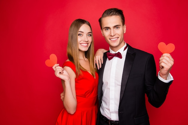 Portrait of young cute couple on a red background