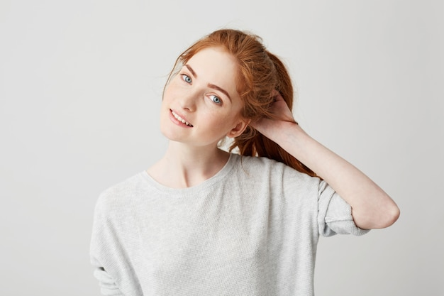 Portrait of young cute redhead girl smiling touching hair .