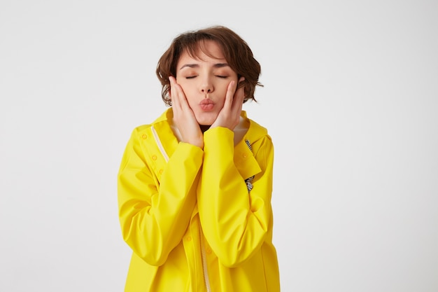 Portrait of young cute short haired girl wears in yellow rain coat, send kiss with closed eyes and touches cheeks, stands over white wall.