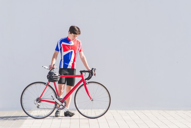 Portrait of a young cyclist standing with a red road bike