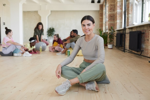Portrait of young dancer sitting on the floor in dance studio and smiling at camera with other group behind her