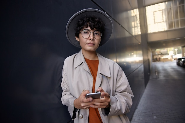 Portrait of young dark haired attractive female with nose piercing standing over city environment, holding mobile phone and looking ahead dreamily, wearing beige coat, foxy sweater and wide grey hat