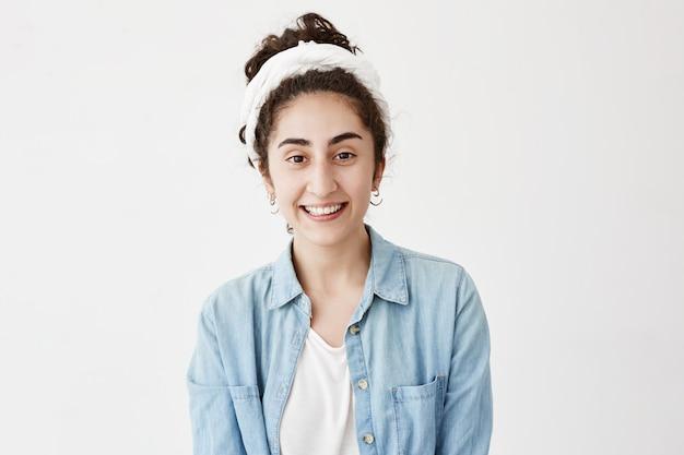 Il ritratto di una giovane donna dai capelli scuri che indossa uno straccio e una camicia di jeans di buon umore dopo aver trascorso i fine settimana con amici o fidanzati, ha impressioni positive.