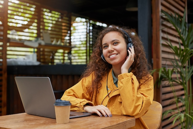 Portrait of young dark skinned curly student girl listens to music and dreaming about weekend party, siting on a cafe terrace, wearing in yellow coat, drinking coffee, works at a laptop.