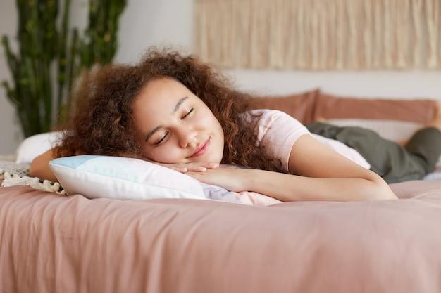 Ritratto di giovane femmina riccia carina dalla pelle scura dormire sul letto, sembra felice, godersi la giornata libera a casa.