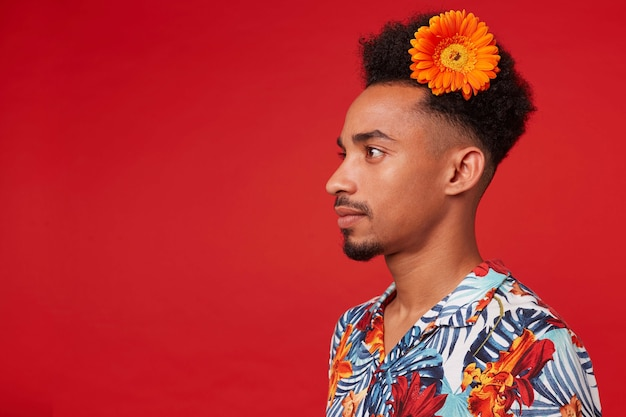 Portrait of young dark skinned guy, wears in hawaiian shirt, looks away with calm expression, with a orange flower in hair, stands over red background.
