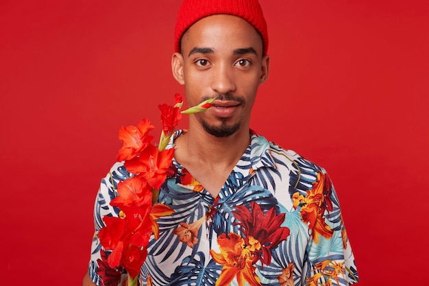 Ritratto di giovane ragazzo dalla pelle scura, indossa camicia hawaiana e cappello rosso, guarda la telecamera con espressione calma, con un fiore rosso, si erge su sfondo rosso.