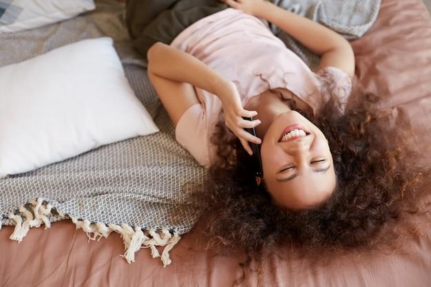 Ritratto di giovane signora dalla pelle scura sdraiata sul letto nella sua stanza e parla al telefono, ampiamente sorridente e godersi la mattina di sole a casa.