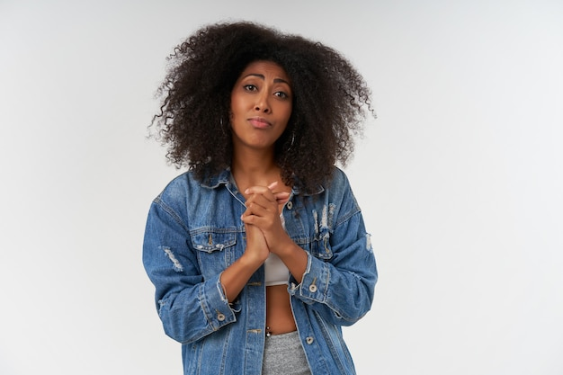 Portrait of young dark skinned lady with curly hair raising folded hands and  plaintively, pursing lips and wrinkling forehead while posing over white wall
