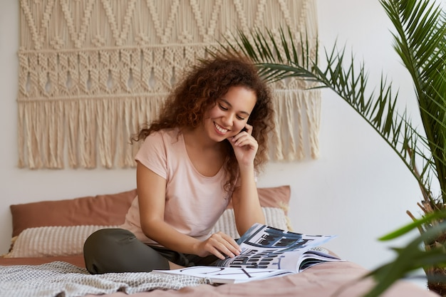 Ritratto di giovane donna dalla pelle scura con i capelli ricci, si siede sul letto e tocca la guancia, sorride e legge una nuova rivista, godersi il tempo libero a casa.