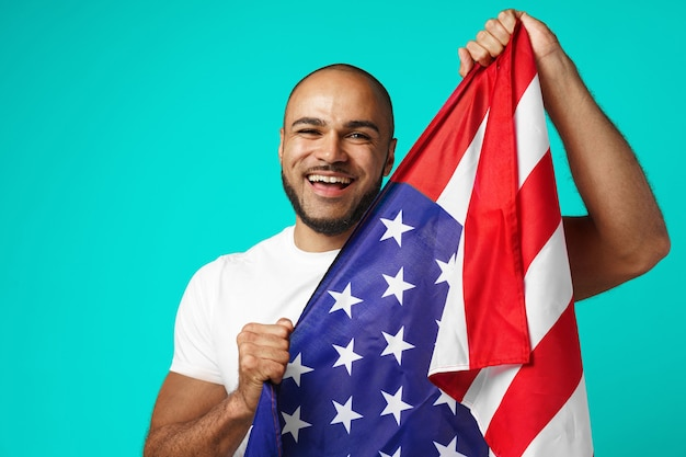 Portrait of young dark-skinned man proudly holding usa flag on turquoise
